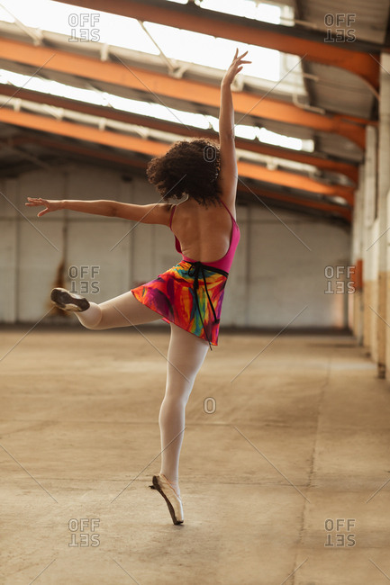 Rear view close up of a young mixed race female ballet dancer standing on one leg on her toes with arms outstretched while dancing in an empty room at an abandoned warehouse