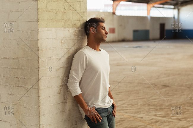 Side view of a young Caucasian man leaning against a pillar with his thumbs in the pockets of his jeans, looking away in an empty room at an abandoned warehouse