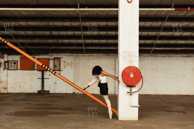 Side view of a young mixed race female ballet dancer wearing pointe shoes dancing standing on one leg on her toes the other leg raised on a structural pole in an empty room at an abandoned warehouse
