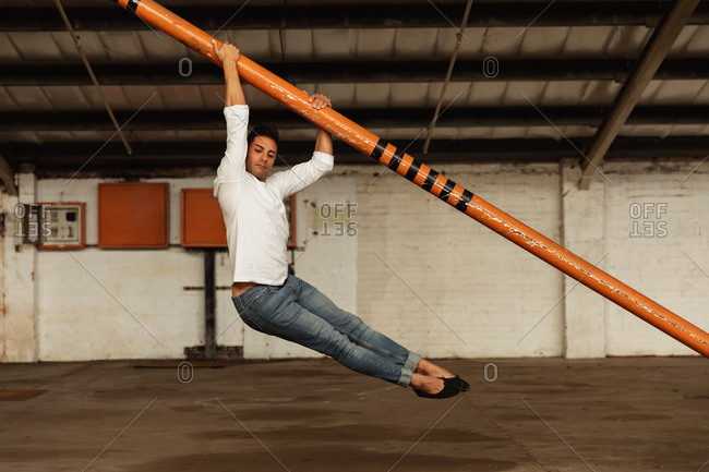 Side view of a young Caucasian male ballet dancer holding a structural pole and dancing with his feet off the ground in an empty room at an abandoned warehouse