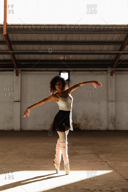 Front view of a young mixed race female ballet dancer wearing pointe shoes standing on her toes in shaft of sunlight with arms outstretched while dancing in an empty room at an abandoned warehouse