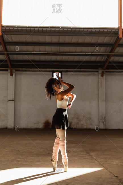 Side view of a young mixed race female ballet dancer wearing pointe shoes standing on her toes in shaft of sunlight while dancing in an empty room at an abandoned warehouse
