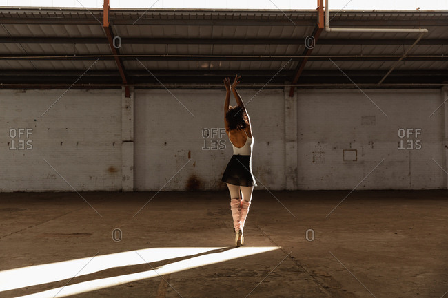 Back view of a young mixed race female ballet dancer wearing pointe shoes standing on her toes in shaft of sunlight with arms raised while dancing in an empty room at an abandoned warehouse
