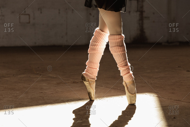 Low section of a young mixed race female ballet dancer wearing leg warmers and pointe shoes standing on her toes in shaft of sunlight while dancing in an empty room at an abandoned warehouse