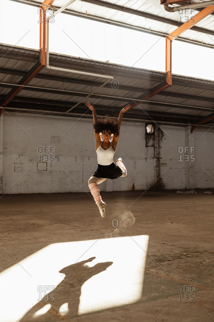Front view of a young mixed race female ballet dancer wearing pointe shoes jumping in the air in shaft of sunlight with arms raised while dancing in an empty room at an abandoned warehouse