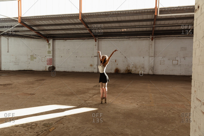 Side view of a young mixed race female ballet dancer wearing pointe shoes standing on her toes with arms raised while dancing in an empty room at an abandoned warehouse