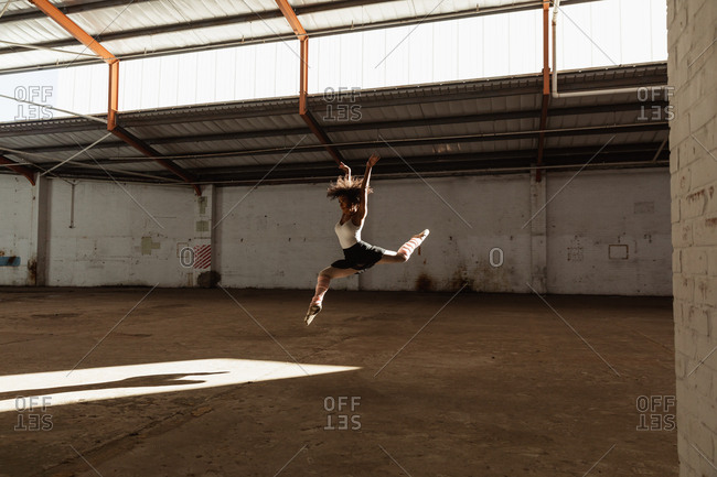 Side view of a young mixed race female ballet dancer wearing pointe shoes jumping in the air in shaft of sunlight with arms raised while dancing in an empty room at an abandoned warehouse