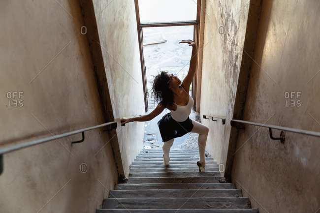 Elevated side view of a young mixed race female ballet dancer dancing on a staircase at an abandoned warehouse