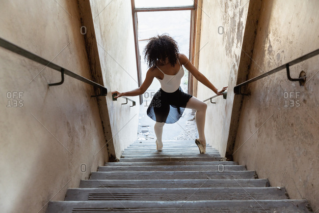Elevated front view of a young mixed race female ballet dancer holding the handrails and dancing at the bottom of a staircase at an abandoned warehouse