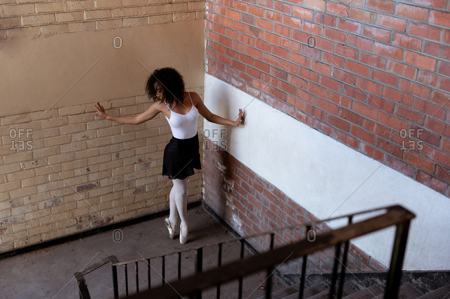 Elevated side view of a young mixed race female ballet dancer holding a dance pose standing on her toes in a corner on a staircase landing in an abandoned warehouse
