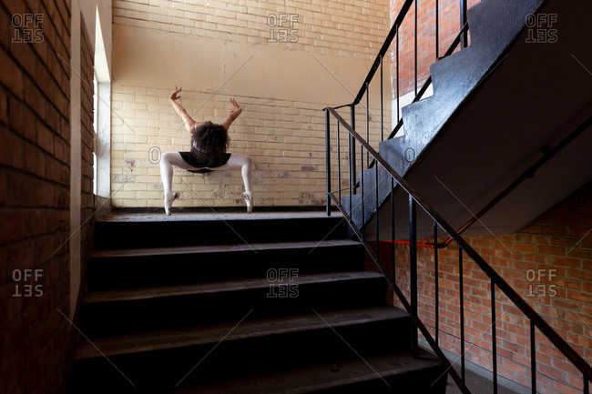 Front view of a young mixed race female ballet dancer holding a dance pose on her toes with arms raised and head down on a staircase landing in an abandoned warehouse
