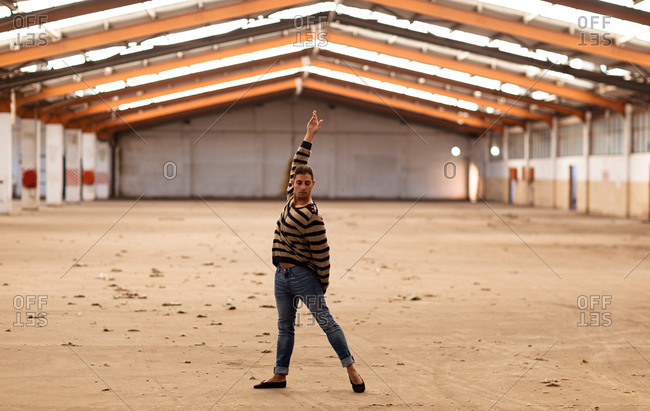 Front view of a young Caucasian male ballet dancer holding a dance pose with arm raised standing in an abandoned warehouse looking to camera