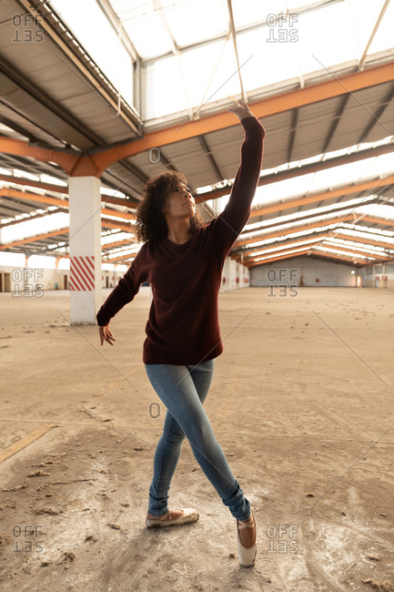 Front view close up of a young mixed race female ballet dancer wearing jeans and pointe shoes dancing with arms outstretched in an abandoned warehouse