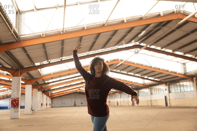 Front view of a young mixed race female ballet dancer wearing jeans and pointe shoes dancing with arms outstretched in an abandoned warehouse