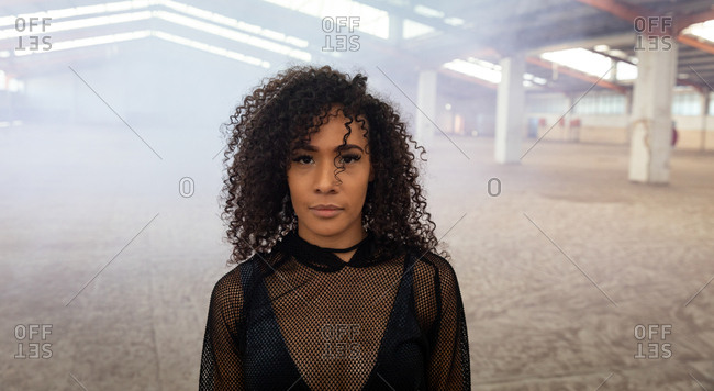 Portrait of a young mixed race woman with shoulder length curly hair wearing a black mesh top looking straight to camera in an abandoned warehouse