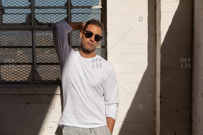 Portrait of a young Caucasian man wearing sunglasses standing against a wall in a shaft of sunlight with one hand behind his head, looking to camera at an abandoned warehouse