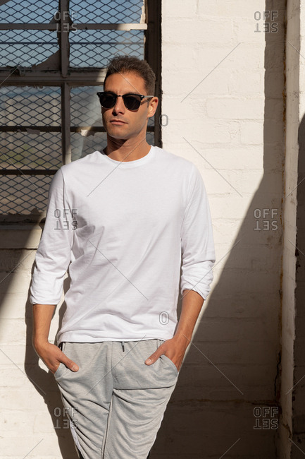 Front view close up of a young Caucasian man wearing sunglasses standing against a wall in a shaft of sunlight with his hands in his pockets, looking away, at an abandoned warehouse