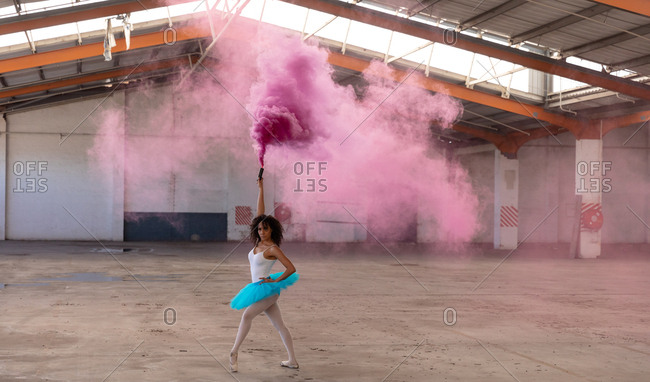 Front view of a young mixed race female ballet dancer wearing a blue tutu and pointe shoes dancing holding a pink smoke grenade in an empty room at an abandoned warehouse