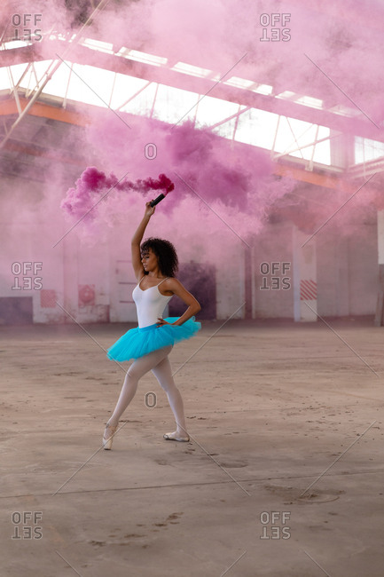 Side view close up of a young mixed race female ballet dancer wearing a blue tutu and pointe shoes dancing holding a pink smoke grenade in an empty room at an abandoned warehouse