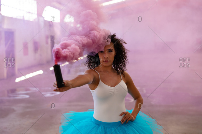 Front view close up of a young mixed race female ballet dancer wearing a blue tutu, holding a pink smoke grenade and looking to camera in an empty room at an abandoned warehouse