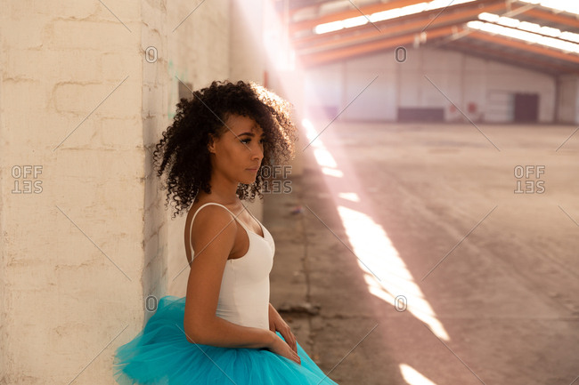 Side view close up of a young mixed race female ballet dancer wearing a blue tutu standing against a wall in an empty room at an abandoned warehouse, a shaft of sunlight in front of her