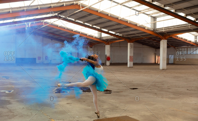 Side view of a young mixed race female ballet dancer wearing a blue tutu and pointe shoes dancing holding a blue smoke grenade in an empty room at an abandoned warehouse