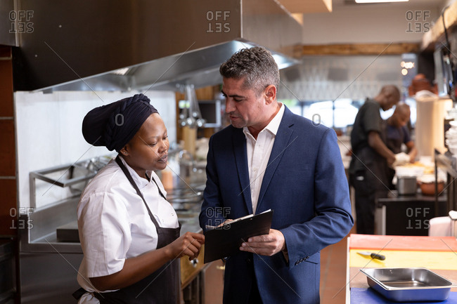 Front view close up of a middle aged Caucasian restaurant manager holding a clipboard and talking with a young African American female chef in a restaurant kitchen