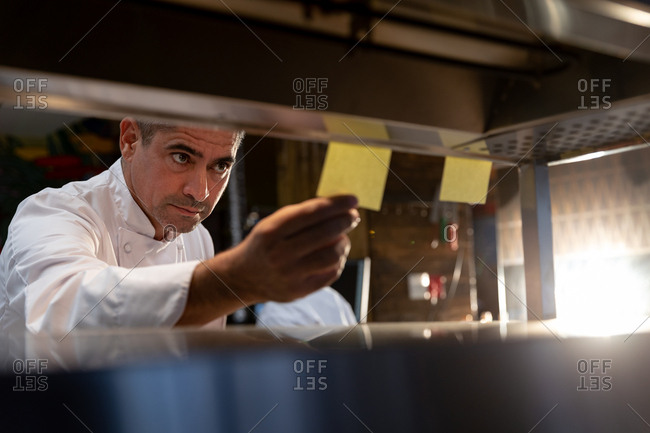 Front view close up of a middle aged Caucasian male chef checking orders at the order station in a restaurant kitchen, seen through shelves