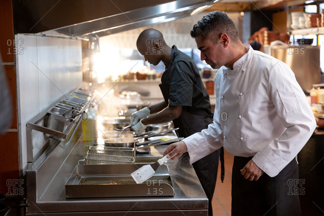 Side view close up of a middle aged Caucasian male chef and young African American male member of the kitchen staff standing over fryers in a restaurant kitchen