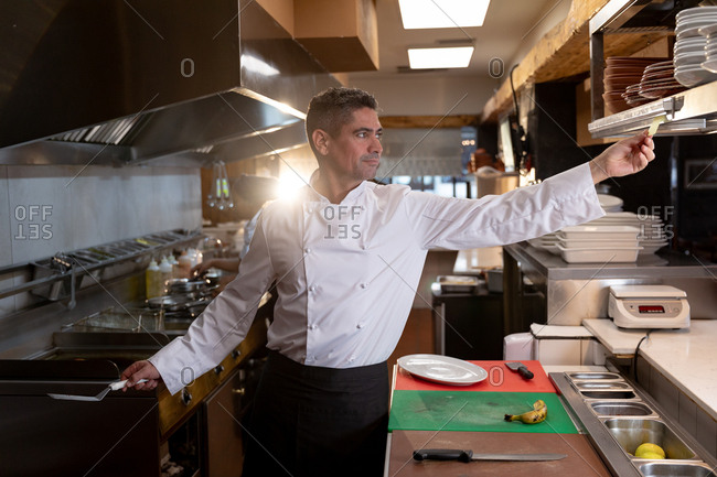 Front view close up of a middle aged Caucasian male chef reaching out to take an order at the order station in a restaurant kitchen