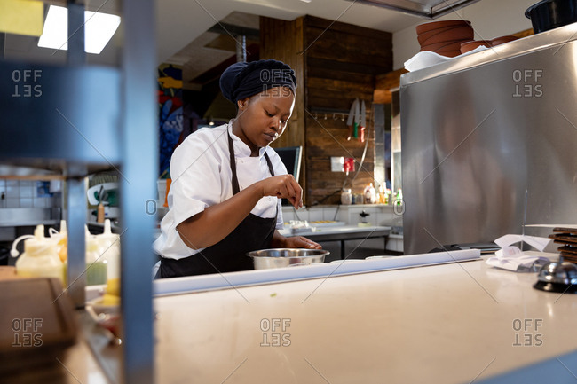 Front view close up of a young African American female chef preparing food in a saucepan in a restaurant kitchen
