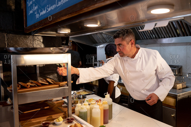 Side view close up of a middle aged Caucasian male chef checking orders at the order station in a restaurant kitchen