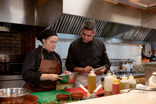 Front view close up of a middle aged Caucasian male chef holding a tablet computer and overseeing the work of a young Caucasian female chef preparing ingredients in a metal bowl in a restaurant kitchen