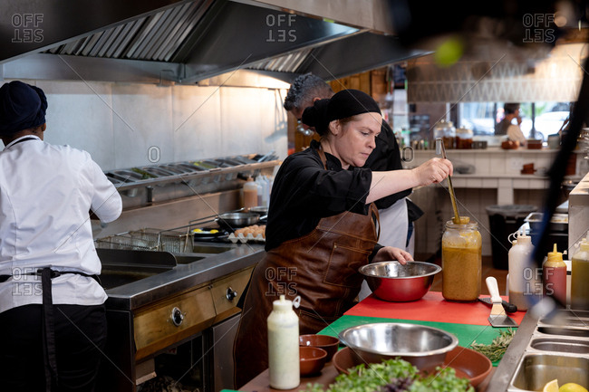 Side view close up of a young Caucasian female chef ladling out a sauce from a jar into a metal bowl in a restaurant kitchen, with other kitchen staff working in the background