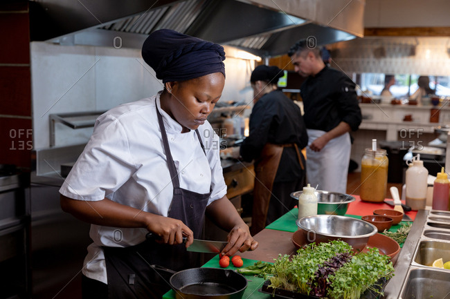 Side view close up of a young African American female chef chopping vegetables in a restaurant kitchen, with other kitchen staff working in the background