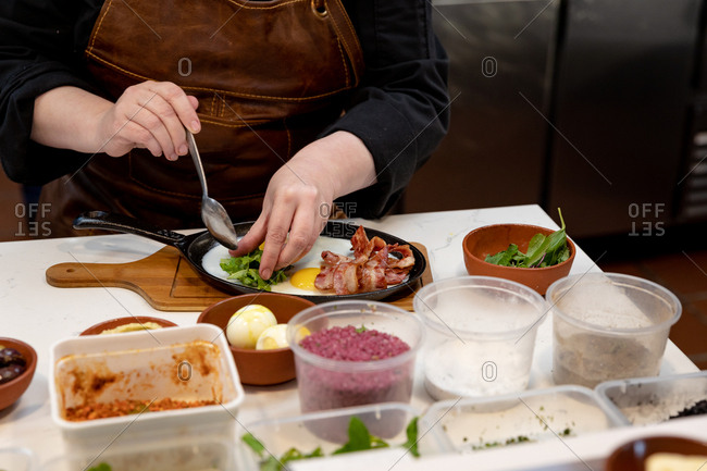 Front view mid section of a Caucasian female chef arranging food to be served in a pan in a restaurant kitchen