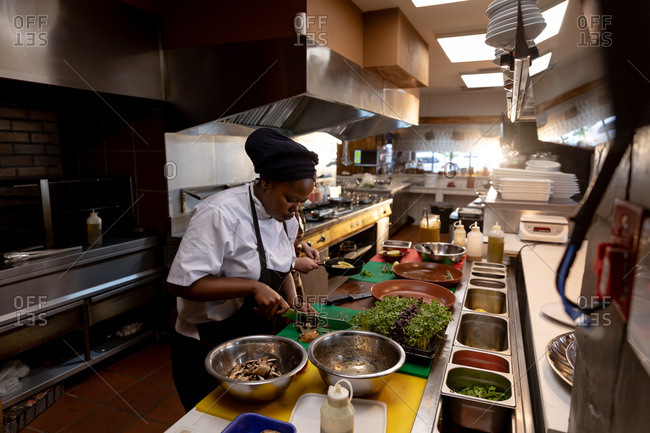 Side view close up of a young African American female chef chopping ingredients on a counter in a busy restaurant kitchen