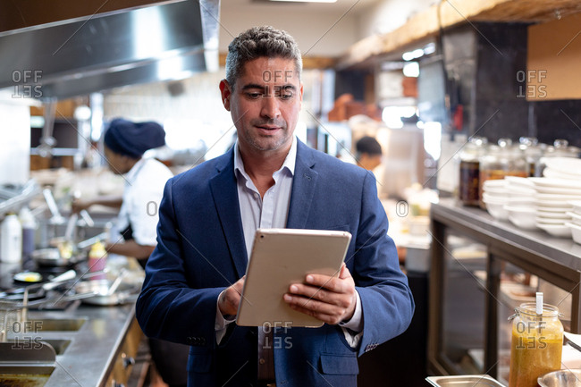 Front view close up of a middle aged Caucasian male restaurant manager using a tablet computer in a busy restaurant kitchen, while kitchen staff work in the background
