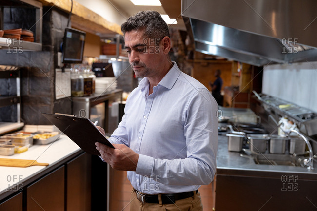 Side view close up of a middle aged Caucasian male restaurant manager writing on a clipboard in a restaurant kitchen