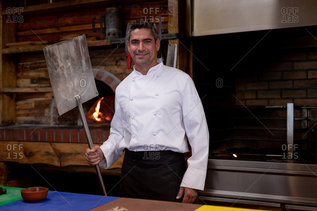Portrait close up of a smiling middle aged Caucasian male chef holding a pizza peel and standing by a pizza oven in a restaurant kitchen