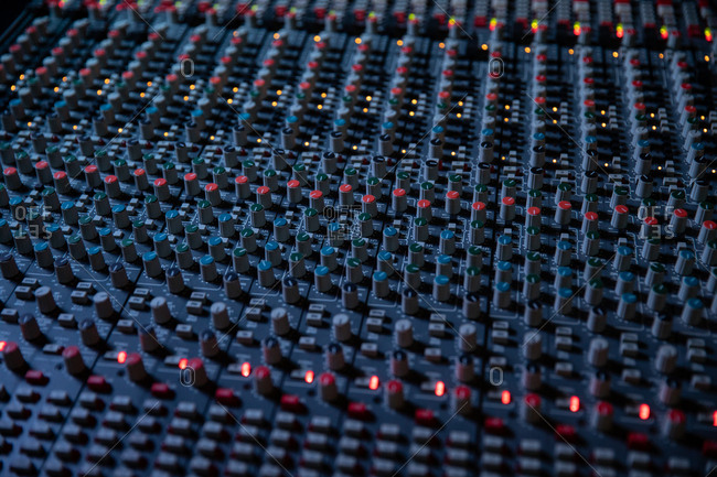 Buttons, knobs and lights of the channel controls on a multitrack mixing desk in a recording studio