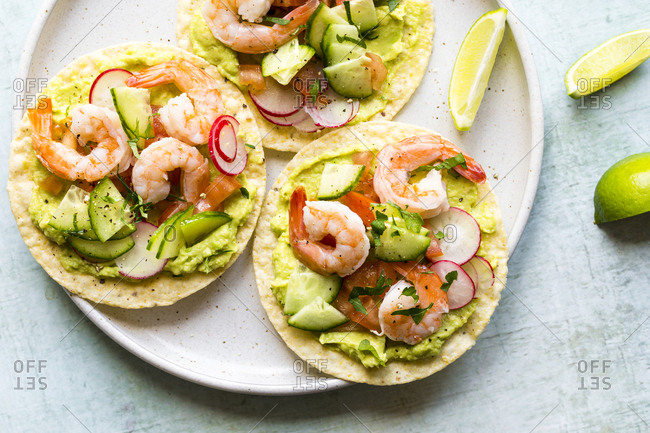 Close up of shrimp tostadas with guacamole, tomatoes and radish