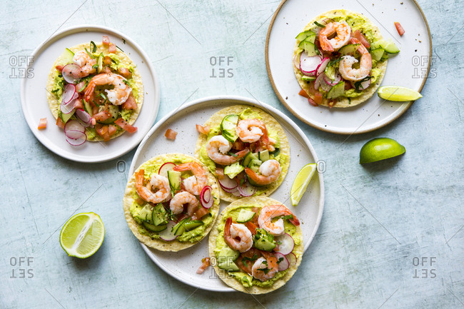 Freshly made shrimp tostadas topped with guacamole, radish, tomatoes, and cucumbers