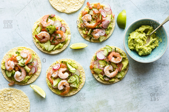 Top view of shrimp tostadas served with homemade guacamole, tomatoes and radish