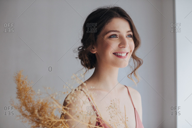 Portrait of beautiful tender young smiling woman in silky nightgown.