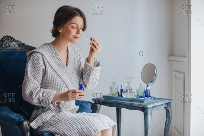 Beautiful Caucasian woman in bathrobe holding cosmetic serum bottle and smelling pipette.