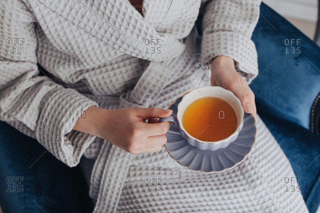 Unrecognizable woman in bathrobe holding cup of tea.