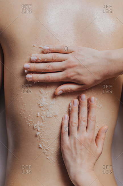 Hands of unrecognizable woman masseuse applying skin scrub on client's back.