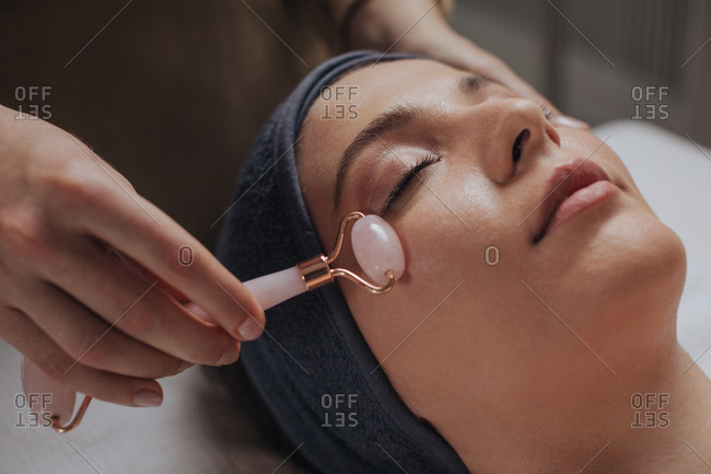 Beautiful young woman enjoying face massage with crystal roller at spa salon.