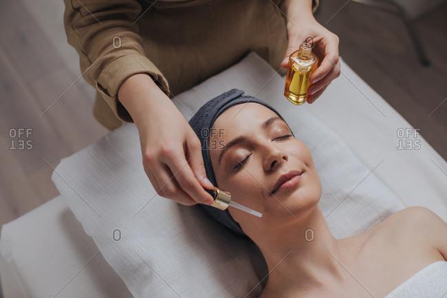 Pretty Caucasian woman enjoying beauty spa treatment at salon.